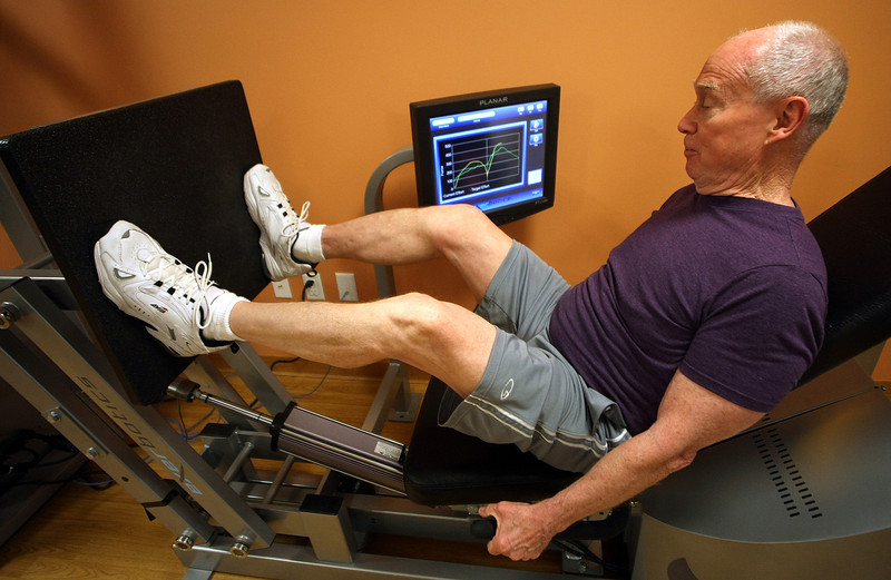Dr. Tom Allen demonstrates a leg press machine designed by Exerbotics and in use at the Inverness Village retirement community in Tulsa.