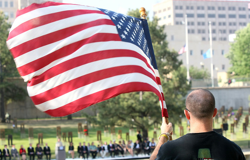 Staff Sgt. Ted Leet holds up an American flag during the 16th anniversary of the 1995 Oklahoma City bombing at the Oklahoma City Memorial Tuesday.  PHOTO BY MAIKE SABOLICH