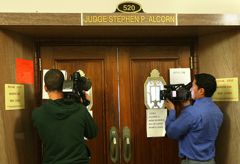 TV crews shoot through the courtroom doors Friday. PHOTO BY MAIKE SABOLICH