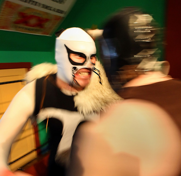 Luchadors grapple at the Elote ring in downtown Tulsa.<br /> <br /> COPY DESK ~~ The guy in White Mask is ~ El Tlacuache (the Possum)  and the other wrestler is El Castor (The Beaver).  The Ring announcer is Gavin Manes