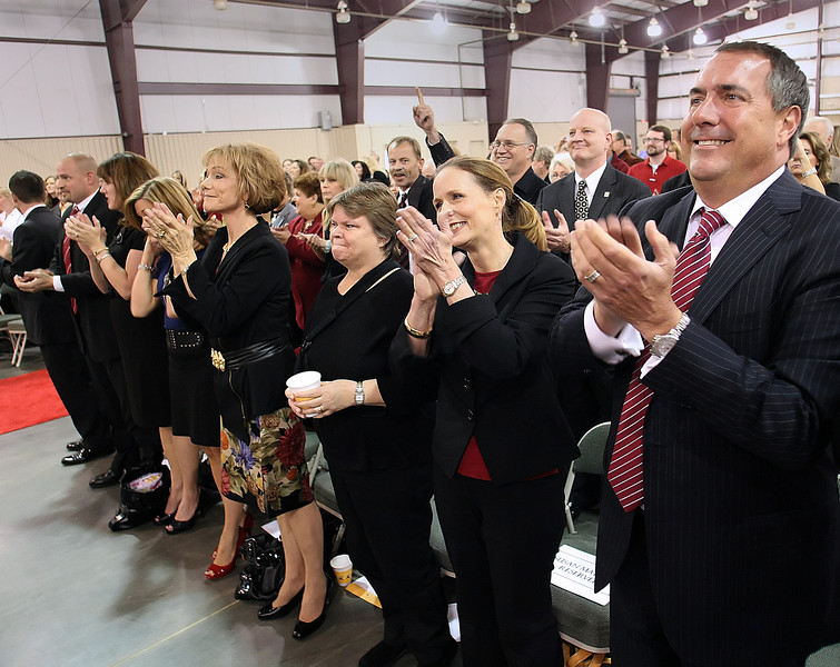 The national CEO of Keller Williams (far right)  Realtors applauds as the merger between his firm and Patterson Realtors is announced at a press conference in Tulsa.