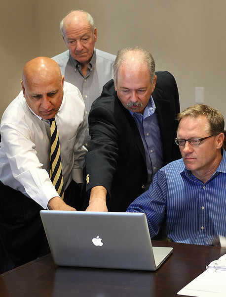 Tulsa businessman Bruce Taylor, Attorney Lee Levinson, diamond wholesaler Neil Bhow and John Snyder, a principal with Brickhugger LLC., look at plans of the redeveloped downtown Tulsa YMCA.