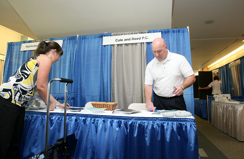 Tabitha Lockhart and Don Phillips set up for the worker's comp symposium at the Reed Center. PHOTO BY MAIKE SABOLICH