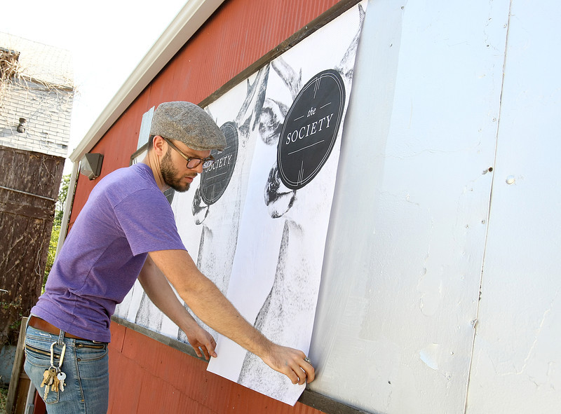 Jerrod Smith hangs up signage for The Society in the Plaza District Friday. PHOTO BY MAIKE SABOLICH