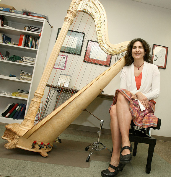 Harpist Gaye LeBlanc has invented a stand to reduce her harp's weight on her shoulder.  PHOTO BY MAIKE SABOLICH