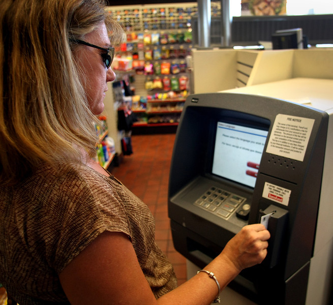 Kyla Davis uses an ATM machine to withdrawal cash.