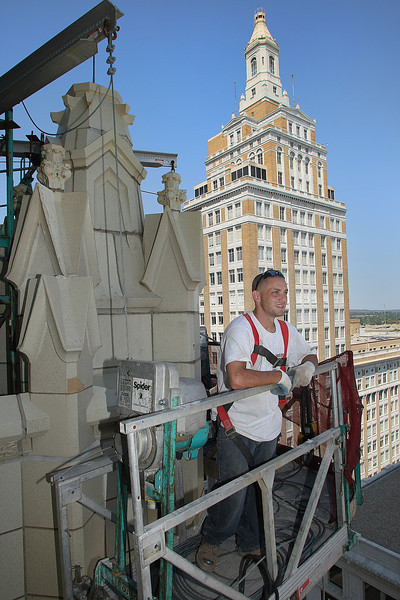 Vince Moscatell of Chicago takes a break from replacing the loose or damaged Terra Cotta trim of the Mid-Continent Building to look out over downtown Tulsa.