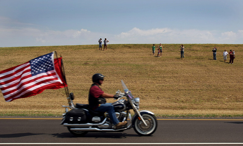 A member of the Freedom Riders passes by people lining the road to pay respects to Sergeant Kirk Owen, killed last week while on patrol in Afghanistan, passes by as he returns home Friday. The 37-year-old father of two was on his second tour of duty. He was one of four soldiers killed in the deadliest week Oklahoma's National Guard has faced since the September 11th terror attacks.