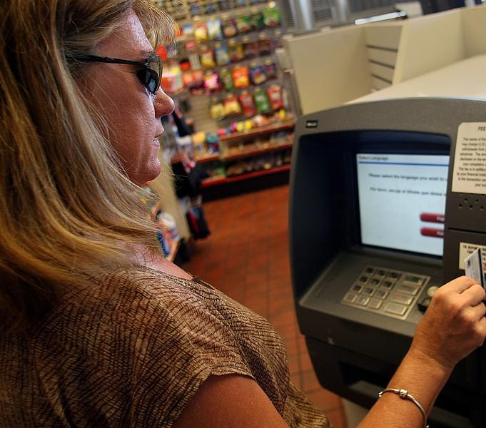 Kyla Davis uses an ATM machine to withdrawal cash.