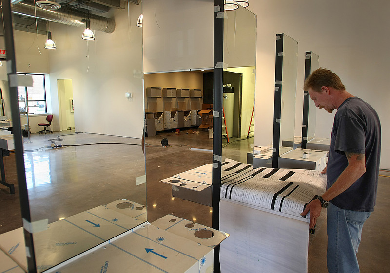Rick Becker, Superintendent with MW Mitchell Construction, consults the blueprints of the new Cosmetology school by Paul Mitchell in the Eastgate metroplex.