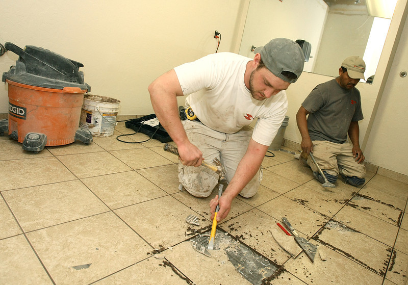 Josh Wainwright and David Bargas work on one of the bathrrom at 50 Penn Place Moday. PHOTO BY MAIKE SABOLICH