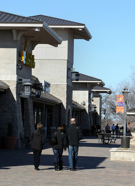 Patrons stroll along the sidewalk at the Jenks RiverWalk Crossing shopping center.  American National Bank of Texas has withdrawn its bid for a $27.86 million summary judgment in the RiverWalk Crossing foreclosure lawsuit in favor of a Sheriffs sale.
