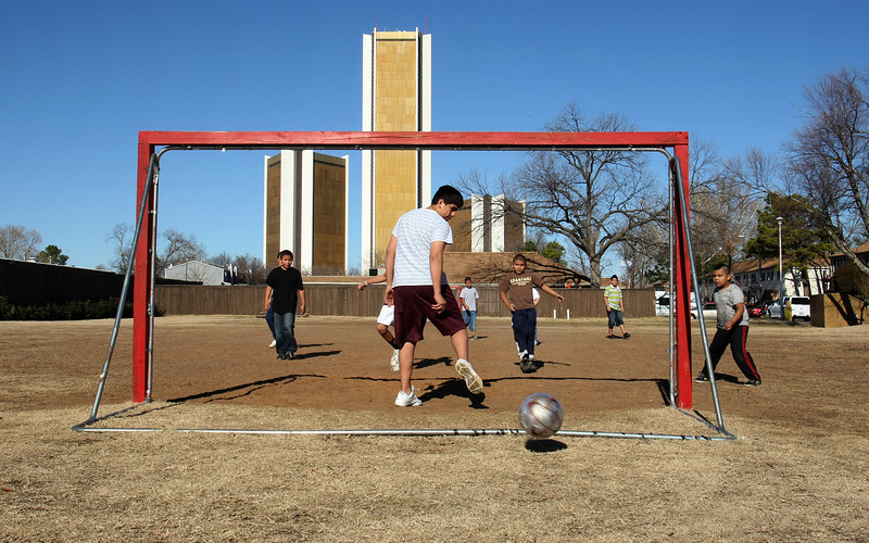 Taking advantage of the recent beautiful weather in Tulsa children play soccer on a field near their home.