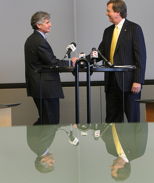 Tulsa mayor Dewey Bartlett (right)shakes hands with Clay Bird at a news conference announcing Birds promotion to Economic Development Director for the city of Tulsa.
