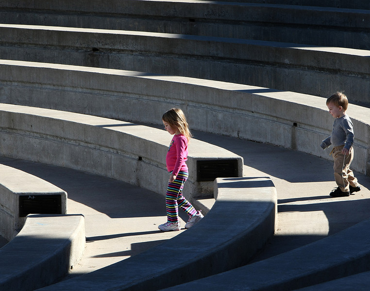 Skylar and Max Smith play on the steps of the Jenks RiverWalk Amphitheater.