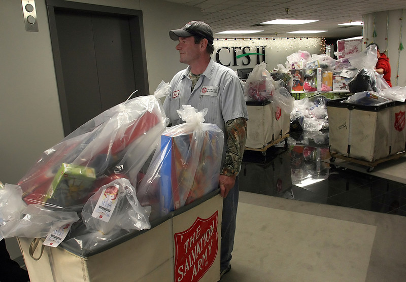 Workmen for the Salvation Army load bins with toys collected for the Angel Tree by the CFS 2 employees.  The 200 employees of the company adopted nearly 300 angels for Christmas.