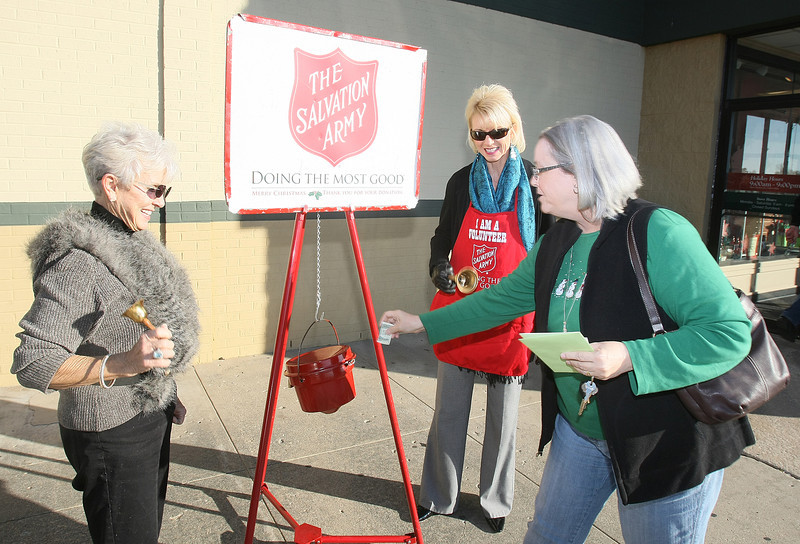 Secretary of Military and Veterans Affairs Rita Aragon and Corporation Commissioner Dana Murphy ring the Salvation Army bell in front of Mardel in Edmond as Ann Ergenbright drops in mony in the bucket Friday.  PHOTO BY MAIKE SABOLICH