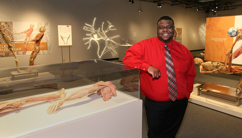 Nef Gibbs, Floor Supervisor for the Bodies Exhibit in Tulsa, takes a moment for a photo among the displays.