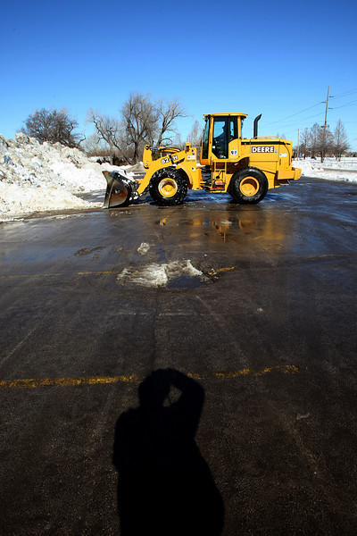 Tulsa City workers us a front loader to scrape snow hauled out of downtown Tulsa by dump into huge piles near the Arkansas River.