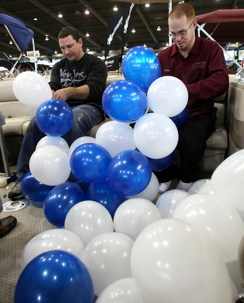 Cross Timbers Marina employee's Pete Mendenhall and Bobby Estes blow up balloons for their displays at the Tulsa Boat Sports & Travel Show at the QT Center in Tulsa.