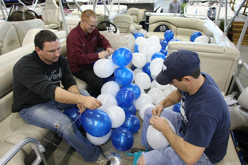 Cross Timbers Marina employee's Pete Mendenhall, Bobby Estes and Dustin Huff blow up balloons for their displays at the Tulsa Boat Sports & Travel Show at the QT Center in Tulsa.