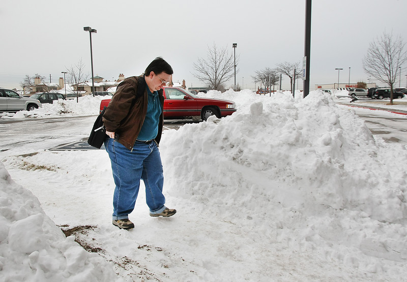 An employee of progressive insurance slogs through piles of snow to get to work Friday in Tulsa.