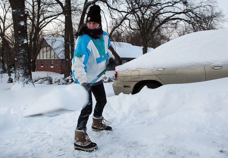 Toni Pike shovels snow to dig her car from under 13 inches of snow that fell in South Tulsa.