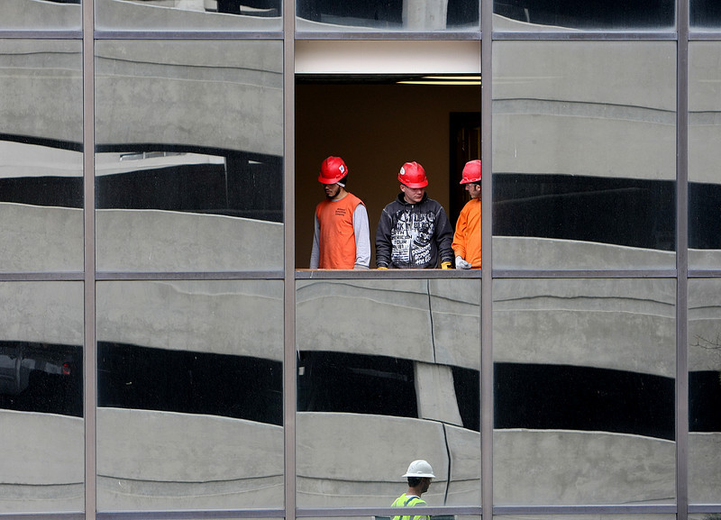 Workmen stand in an open fifth floor window of the Houston Center in Tulsa.  The window had been removed to allot drywall to be loaded through the window onto the jobsite.