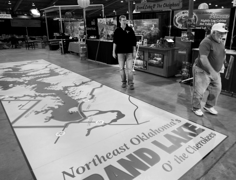 Tan Jones & Art Box inspect a sticker of the Grand Lake area they had just installed at the Tulsa Boat Sports & Travel Show at the QT Center in Tulsa.