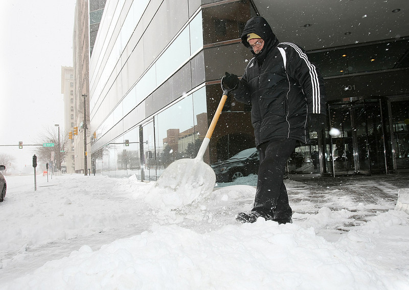 Robert Bell shovels snow in front of Corporate Tower downtown Wednesday. PHOTO BY MAIKE SABOLICH