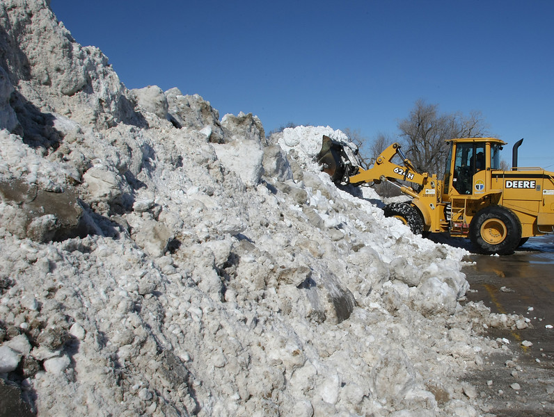 A front loader scrapes snow hauled out of downtown Tulsa by dump trucks into a huge pile near the Arkansas River.