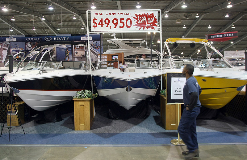 A passerby looks at a show special at the Tulsa Boat Sports & Travel Show at the QT Center in Tulsa to get a few E-mails read.
