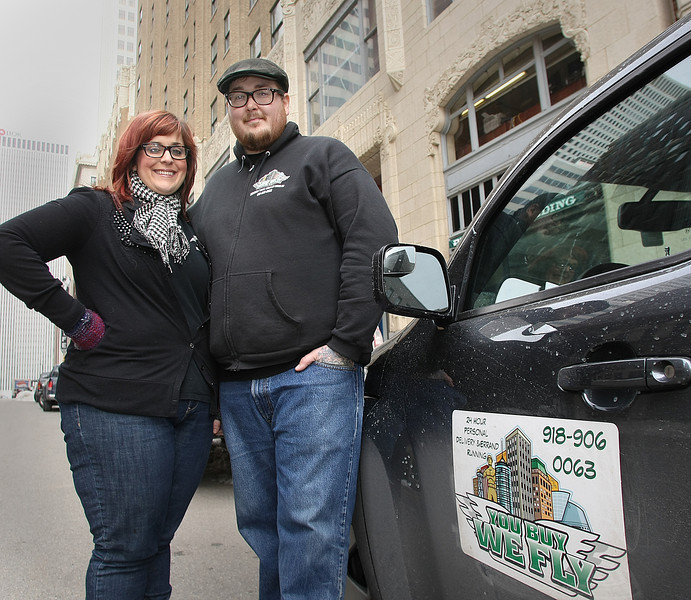 Lauren and Justin Orcutt, Owners of You Buy We Fly, take a moment for a photograph while making a downtown Tulsa delivery Tuesday.