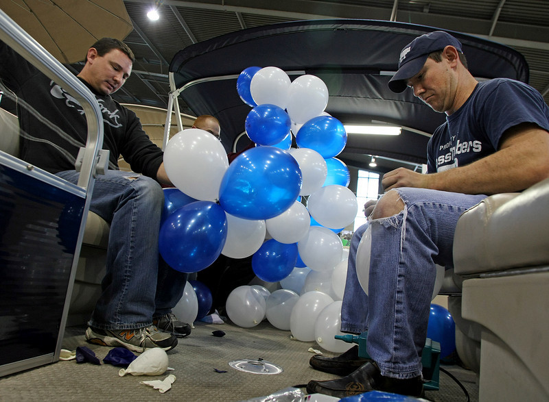 Cross Timbers Marina employee's Pete Mendenhall and Dustin Huff blow up balloons for their displays at the Tulsa Boat Sports & Travel Show at the QT Center in Tulsa.