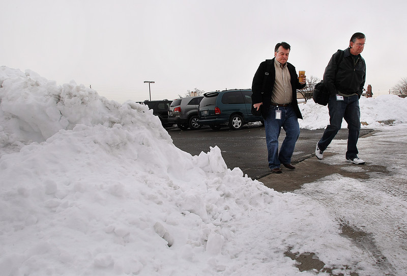 Employee's slog through piles of snow to get to work Friday in Tulsa.