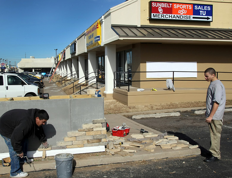 Workman lay stone as part of a facelift for the Sunbelt Plaza Strip Center purchased for $1.9 Million to a California investor.