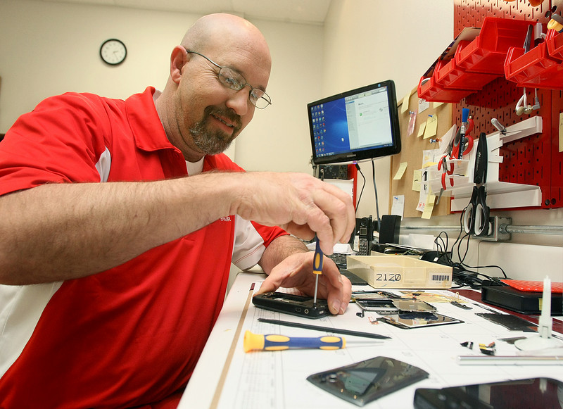 Lee Moody, store manager at Cell Phone Repair in Moore, works on a BlackBerry Thursday. PHOTO BY MAIKE SABOLICH