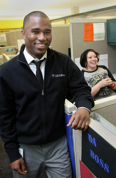Jon Lomax, director of U.S. Cellular's Tulsa Customer Care Center, chats with customer care specialist Shawanda Sims.