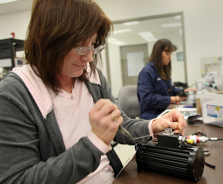 Glenda Burrus and Joella Nolen assemble aircraft components at the Technology Development Group in Shawnee.
