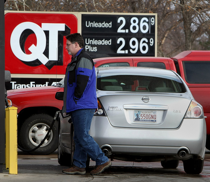 A motorist fuels his car at a QT store in Tulsa. The price of gasoline at the pump has jumped 30 cents a gallon since November 30th.