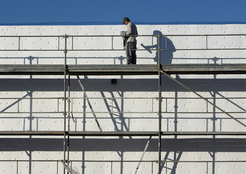 A workman inspects foam insulation he had just finished installing on a commercial building in South Tulsa.