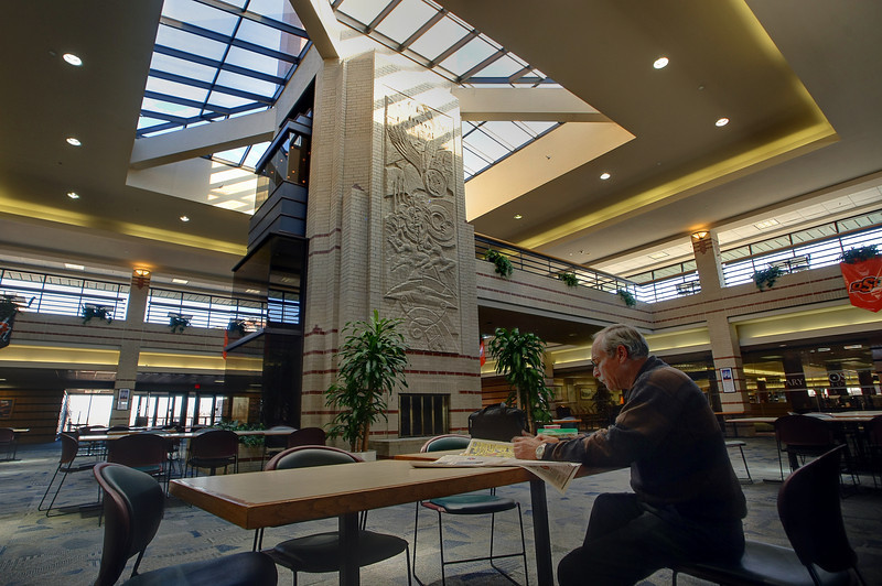 An instructor takes his lunch in the main hall at the OSU Tulsa Campus.