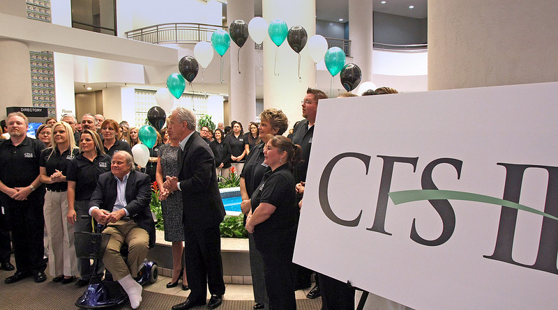 The employees of CFS II gather in the lobby for a ribbon cutting celebrating hiring their 100th Employee.