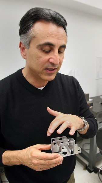 Harmik DerSahakian, Co-Owner of the Technology Development Group in Shawnee, inspects an aircraft component his company is developing.
