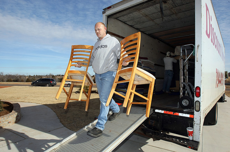 Rusty Wortham with Discount Moving carries chairs out of the company truck during a household move to South Oklahoma City Friday. PHOTO BY MAIKE SABOLICH