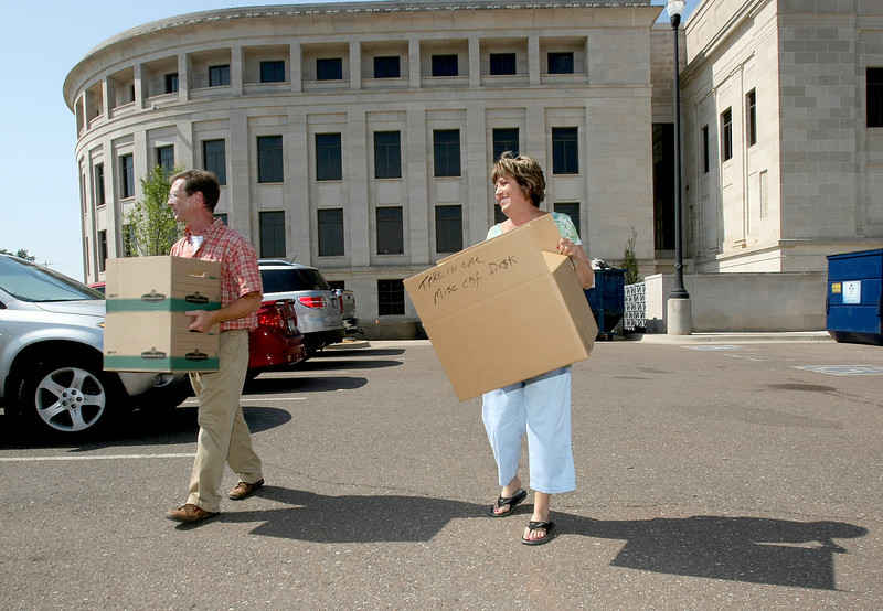 Allen Smith and Molly Reid carry empty boxes out of the new Supreme Court building to fill them back iup with other items to move from the capitol Friday. PHOTO BY MAIKE SABOLICH