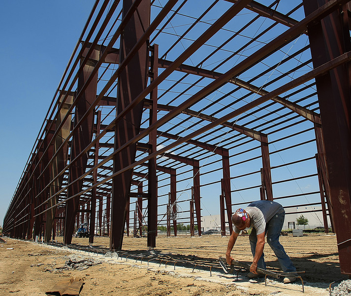 Joe Gennet works on the foundation of a new building at the Cherokee Industrial Park in North Tulsa.