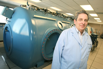 Dr. Herbert Meites with the Integris Paul Silverstein Burn Center in front of a hyperbaric chamber. PHOTO BY MAIKE SABOLICH