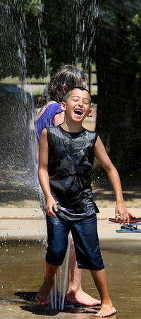 Ramond Wilcox laughs after being bumped off the water jets by Abigail Carter.  The kids were keeping cool in the 100+ degree heat  at the  RiverParks Water Park in South Tulsa.