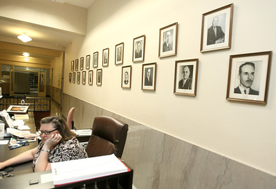 Michelle Kaszouski, secretary to the municipal council, sits in front of city attorney photos which were rearranged during this weekend's break-in at City Hall.  PHOTO BY MAIKE SABOLICH